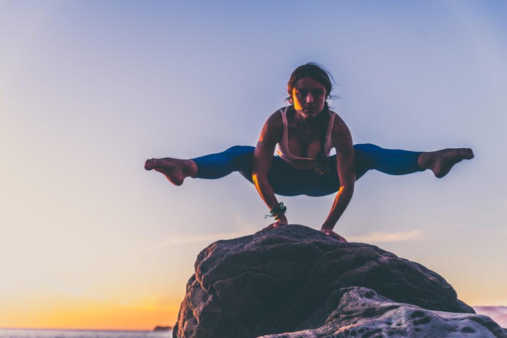 woman yoga balance training on rock on beach - learn kung fu online