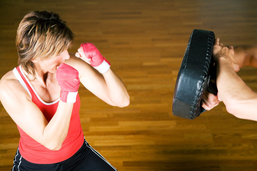 woman training martial arts on pad - learn kung fu online