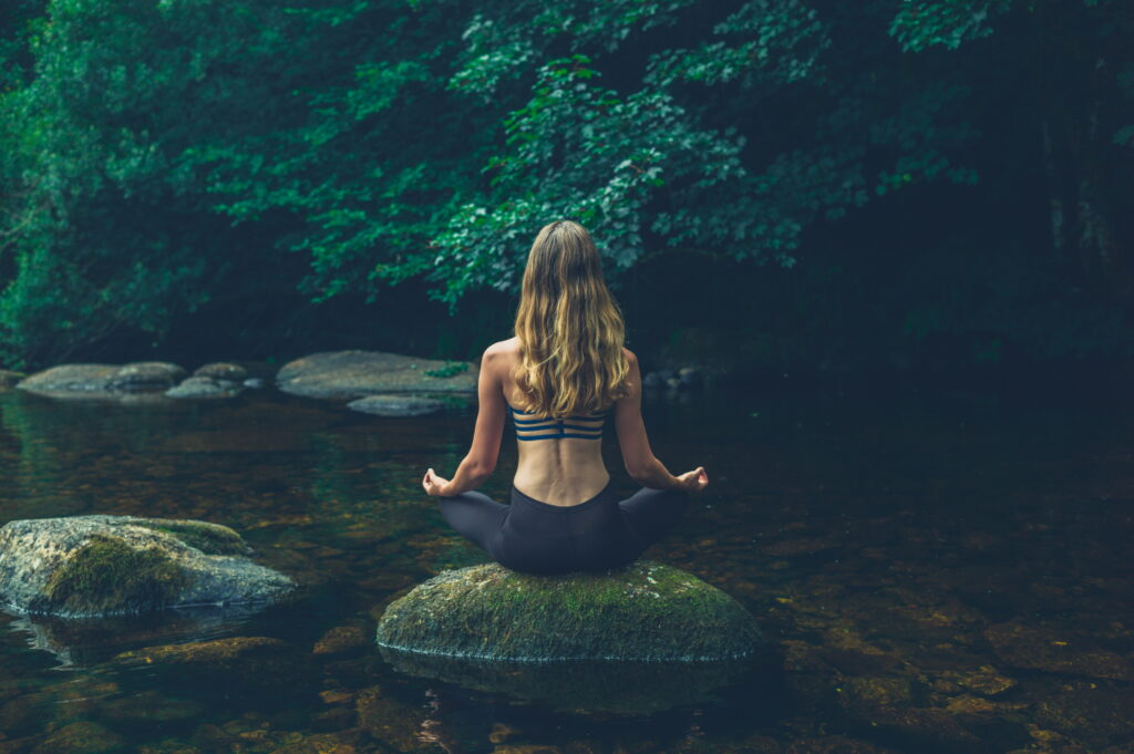 A young woman is meditating on a rock in the river - learn kung fu online