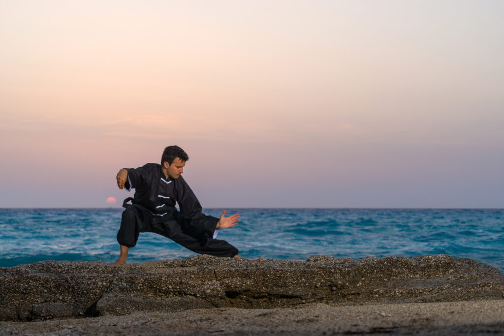 Man doing Kung Fu on beach with sunset - learn kung fu online