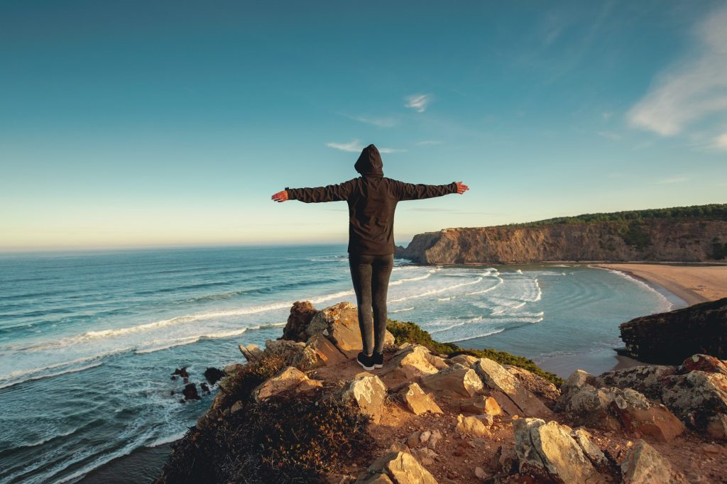Freedom standing on rocks facing sea