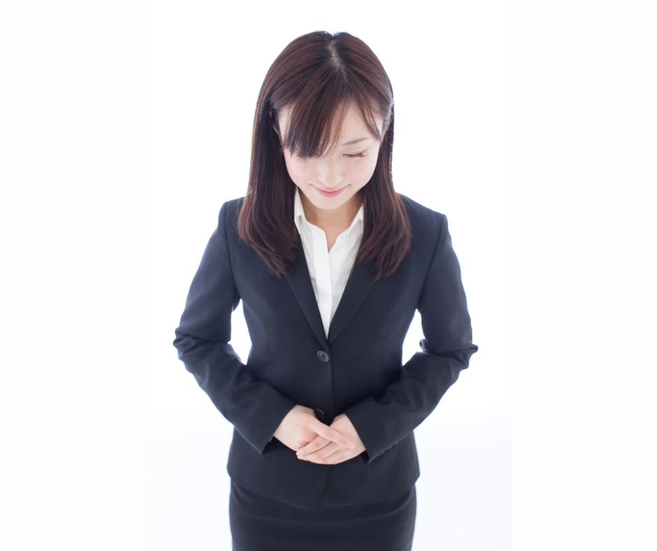 Asian woman in suit with hands clasped showing focus and calmness