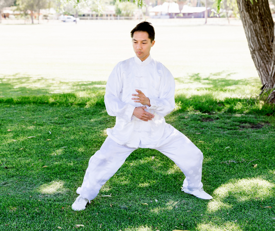 Asian man in white uniform doing Tai Chi in park